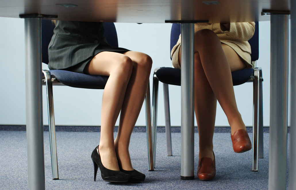 Legs of two businesswomen under the meeting room table